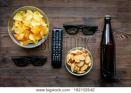 snacks for watching TV film with glasses and control on wooden desk background top view mock-up