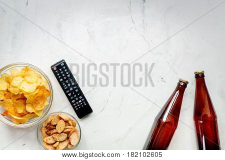 snacks for watching sport match with TV control and beer on white deskbackground top view mock-up