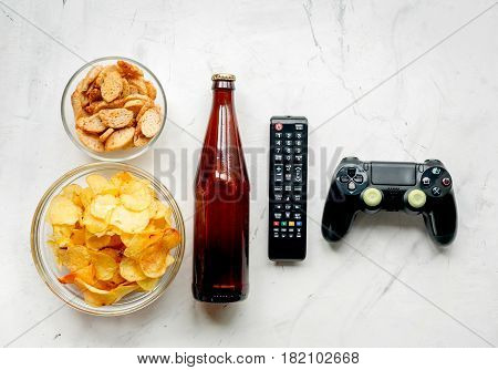 snacks for playing video games with joypad and beer on white desk background top view mock-up