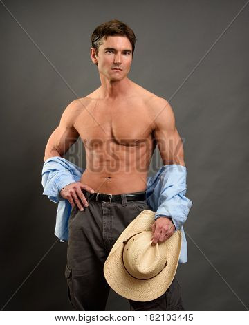 The handsome cowboy is holding his hat.
