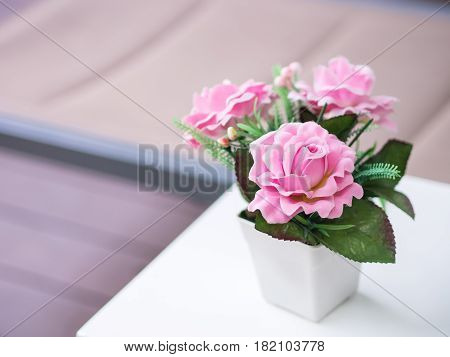 Bouquet Pink roses in the white vase Artificial or fake flowers decorated on white table with wooden background.