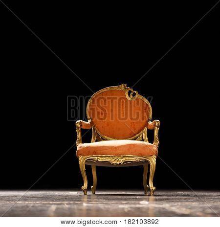 Vintage orange chair on the theater stage against dark black background