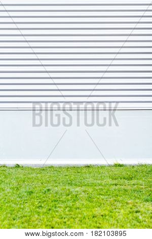 Metallic wall with green grass. Modern urban background