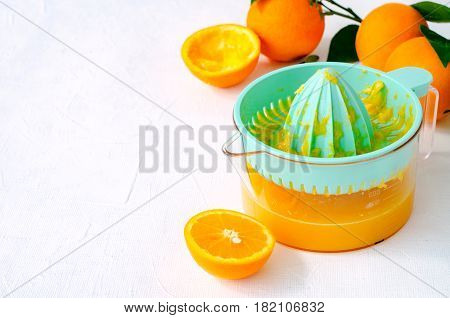 Freshly squeezed orange juice in turquoise juicer on white background, horizontal, copy space