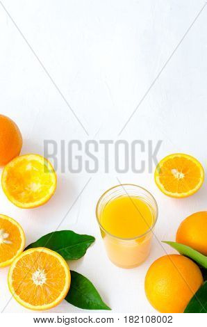 Freshly squeezed orange juice in glass on white background, vertical, top view, copy space