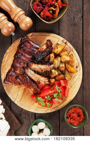 Honey glazed pork ribs with roasted potato and tomato salad