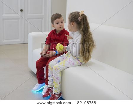 Small boy and girl sitting on the sofa and talking. Girl is holding green apple. Boy is wearing glowing led sneakers.