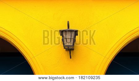 Lamp on orange wall with curved walls bright colors.
