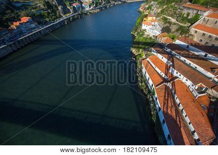 View of Douro river with the shadow of Dom Luis I bridge, Porto, Portugal.