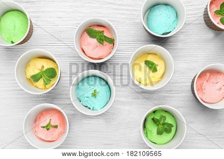 Ice cream collection in paper cups on wooden background