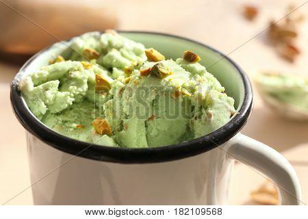 Pistachio ice cream with chopped nuts in mug, closeup