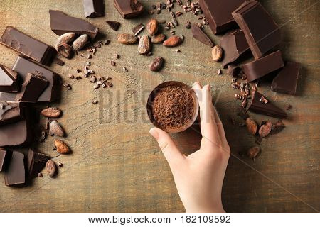 Woman holding bowl with aromatic cocoa powder and pieces of chocolate on wooden background