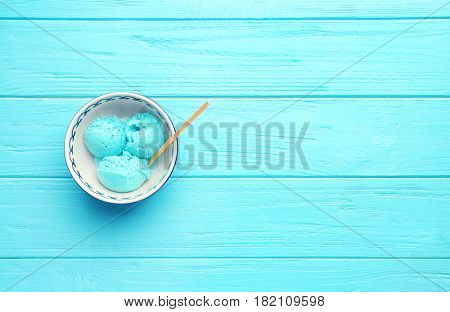 Tasty mint ice cream in bowl on wooden background