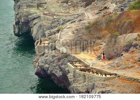tourists walk along a path in the mountains to the sea Sichang Island Chonburi Province Thailand