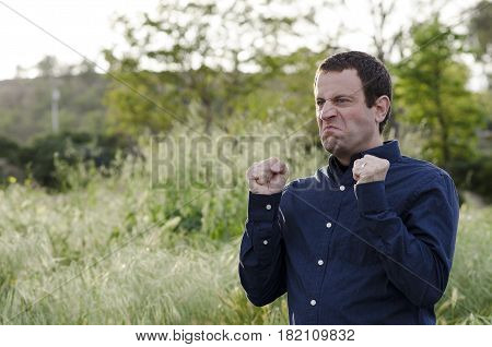 Angry man outdoors with fist clenched making an angry face.
