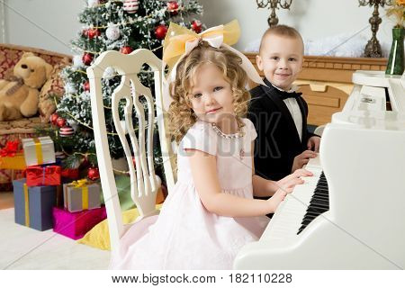Solemnly dressed little boy and girl into the night, sitting at a white piano. Children put hands on the keys.