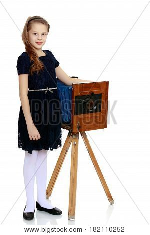 Cute little girl posing next to an old photo camera.Isolated on white background.