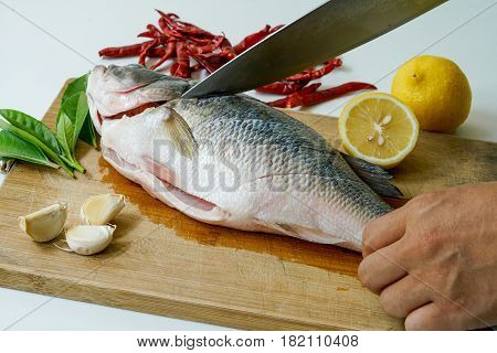 Cutting the fish for Seabass steam with lemon garlic and chili - Thai food isolated on white background