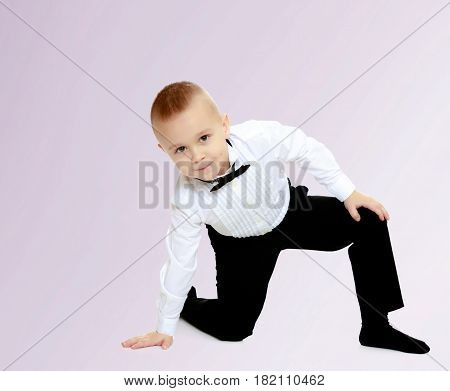 Elegant little boy in black pants , white shirt and black tie. Standing on one knee.