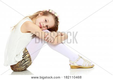 Beautiful little long-haired Caucasian girl posing in Studio.The girl is sitting sideways on the floor hugging her knees.Isolated on white background.