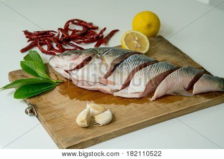 Preparing for Seabass steam with lemon garlic and chili - Thai food isolated on white background