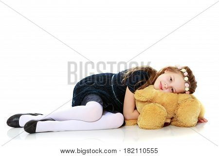 Beautiful little girl in a blue dress is hugging a large Teddy bear . Girl sitting on the floor.Isolated on white background.
