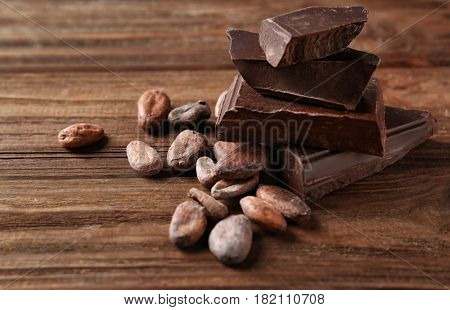 Cocoa beans and pieces of chocolate on wooden background