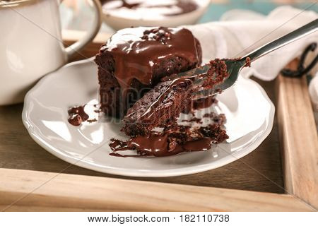 Fork with piece of cocoa brownie and cake on plate, closeup