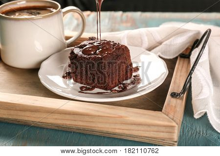 Pouring melted chocolate onto tasty cocoa brownie on plate
