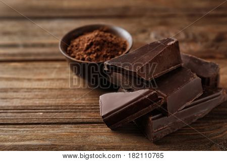 Pieces of tasty dark chocolate and bowl with cocoa powder on background
