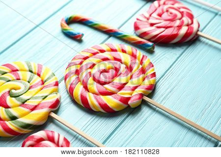 Composition with tasty colorful lollipops on wooden background, closeup