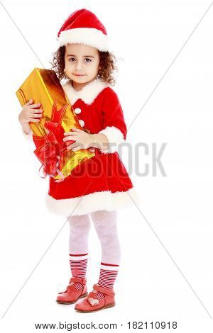 Cute little curly girl in a coat and hat of Santa Claus holding a box with a gift.Isolated on white background.
