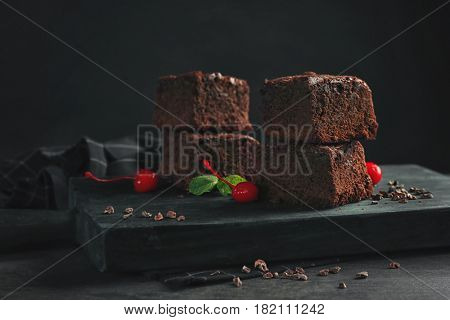 Wooden board with delicious cocoa brownies on table