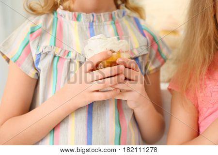 Cute little girl with tasty dessert, closeup