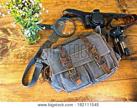 Bleu Satchel With Camera Tripod and Magnefying Glass Sitting on Wooden Table
