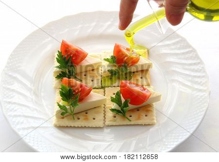 Cheese biscuits with tomatoes and oil on white