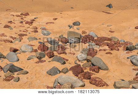 Small stones on a beach in Goa, India, on a sunny day
