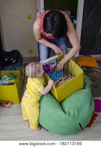A small child is playing with toys in a box with mom in the children's room