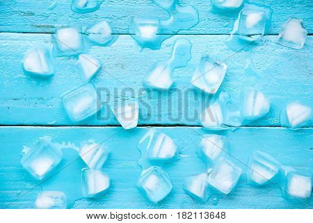 The Cold Ice Cubes Are Partial Melt On Blue Wood Background