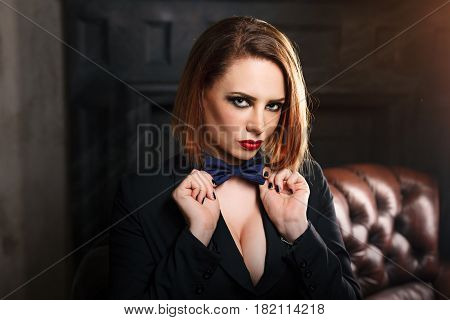 Young attractive girl in a butterfly jacket and tie. Femme fatale. The artsy fashion. Evening makeup smokey eye. She straightens the bow tie
