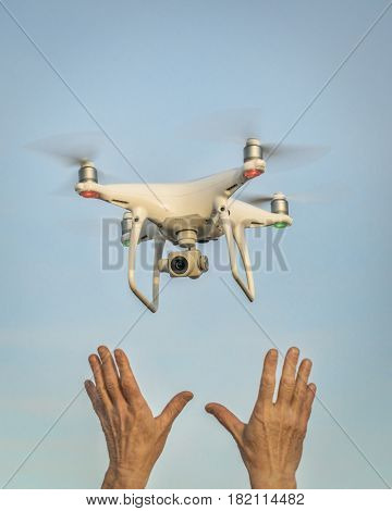 CARR, CO, USA - APRIL 12, 2017:  Launching DJI Phantom 4 pro quadcopter drone - operator hands and drone against sky.