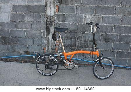 Orange folding bicycle on the road .