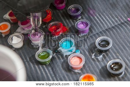 Tattoo artist mixing colors into small cup for ink. Closeup