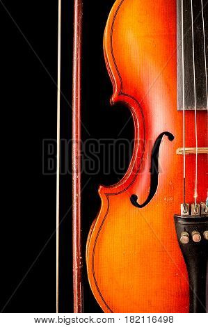 Violin and bow isolated on black background. A musical stringed instrument for musical performance