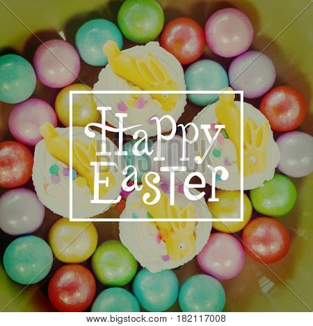 Happy easter against colorful chocolates and cupcakes in bowl