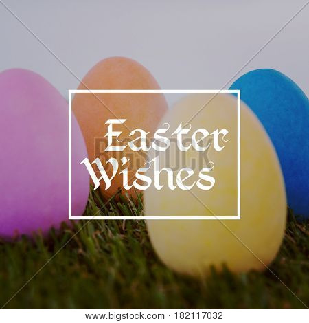 Easter greeting against painted easter eggs arranged on grass