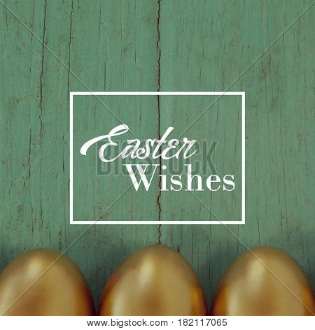 Easter greeting against golden easter eggs arranged on wooden surface