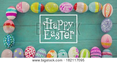 Happy easter against painted easter eggs arranged in rectangle shape on wooden plank
