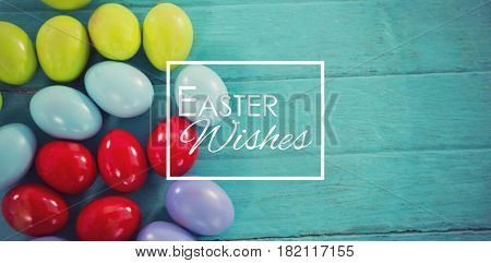 Easter greeting against colorful easter eggs on wooden table