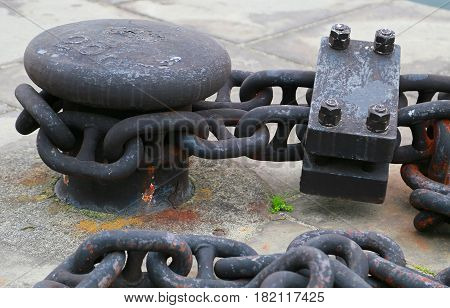 Black metal bit and chain for harbor anchorage